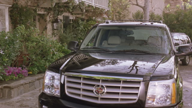vídeos de stock, filmes e b-roll de medium angle of black cadillac escalade parked in front of upper class multi-story house. see pruned plants and bushes in planters. see stone driveway. - cadillac
