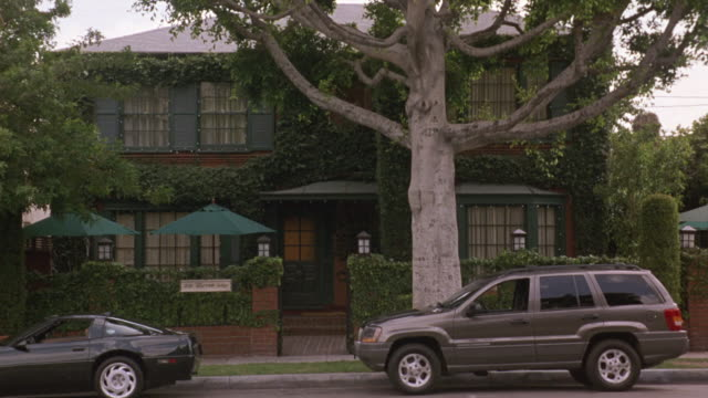 medium angle of two story upper class brick house with green accents. see brick wall covered with vines in front of house. see black corvette and grey suv parked in front of house. see green umbrellas in front of house. camera moves left. could be restaur - brick house stock videos & royalty-free footage