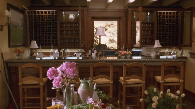 medium angle establish of wet bar. see chairs lined at counter. see bottles and wine glasses against back wall. see table in foreground with flower arrangement and pots. see window in background. could be interior of house or restaurant. - bar点の映像素材/bロール
