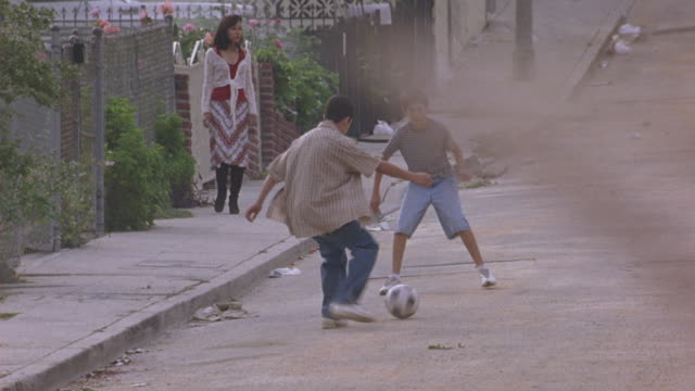 vídeos de stock, filmes e b-roll de medium angle of two boys kicking soccer ball around in middle of street of residential area. see woman in skirt standing on sidewalk. shot pans up as yellow school bus drives down street from background. as bus passes, shot pans down to pavement. lower cl - méxico