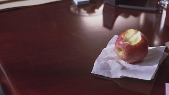 close angle of half eaten apple sitting on napkin on top of desk. - napkin stock videos & royalty-free footage