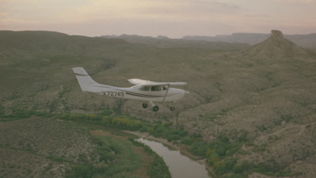 aerial of white single engine propeller plane flying over rocky mountainous terrain. see pink and orange sky and sun in background. see some green on mountains below. see small river below as plane dips close to desert landscape. - propeller aeroplane stock videos & royalty-free footage