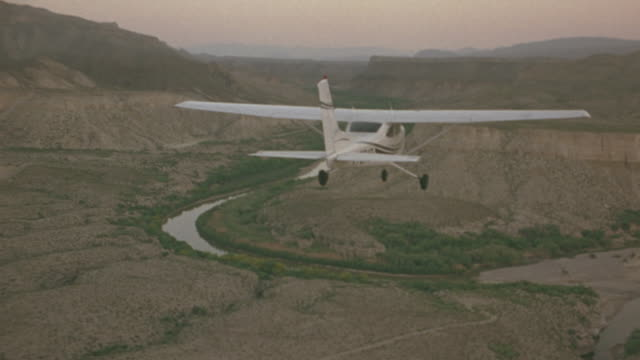 aerial of white single engine propeller plane flying over rocky mountainous terrain. see pink and orange sky. see some green on mountains below. see small river below as plane dips close to desert landscape. - propeller video stock e b–roll