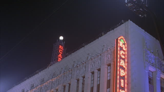 medium angle of the el capitan theatre building top half and sign lit. movie theaters. hollywood blvd. neon signs. - el capitan theatre stock videos & royalty-free footage