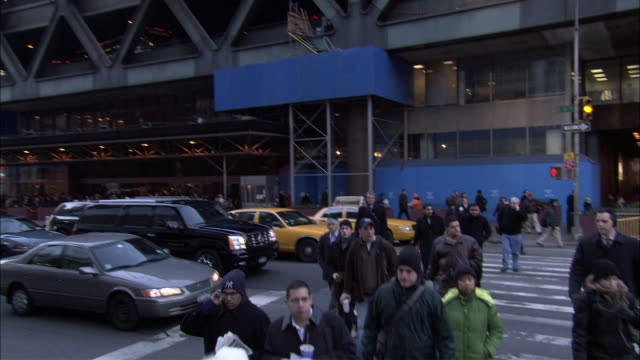 pan right to left of pedestrians, people walking across city street at intersection outside of port authority bus terminal. midtown manhattan. - port authority stock videos & royalty-free footage