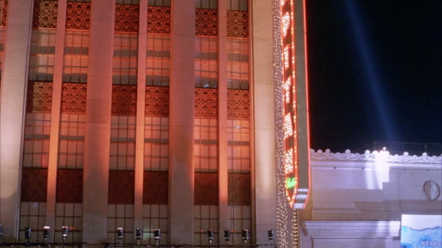 "medium angle of el capitan theatre. beams of light from klieg lights or spotlights scan back and forth. red light reflected off of building. see neon sign vertically posted on side of theatre that says ""el capitan"". movie theaters. hollywood blvd. could b - el capitan theatre stock videos & royalty-free footage"