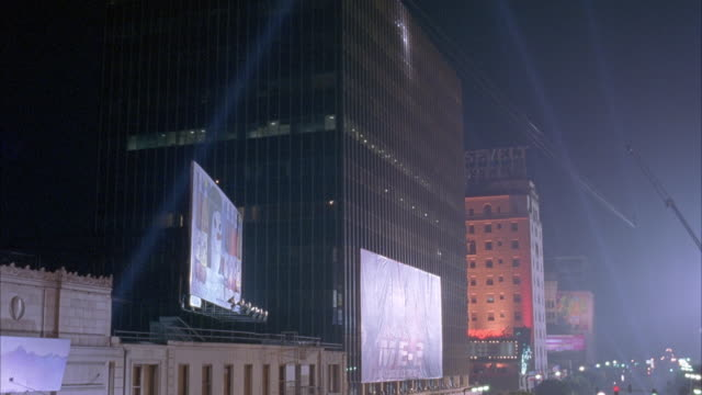 wide angle of buildings on hollywood boulevard. see part of el capitan theatre and roosevelt hotel. beams of light from klieg lights or spotlights move back and forth. movie theaters. could be movie premiere. - suchscheinwerfer stock-videos und b-roll-filmmaterial