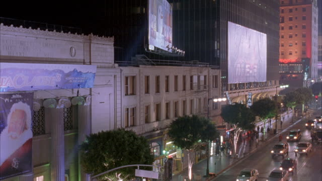 vidéos et rushes de wide angle of buildings on hollywood boulevard. see part of el capitan theatre and roosevelt hotel. beams of light from klieg lights or spotlights move back and forth. movie theaters. could be movie premiere. see ad, possibly for a movie, with santa claus - hollywood boulevard