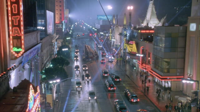 ZOOMS IN AND PANS FROM FG TO BG ALONG HOLLYWOOD BLVD. CARS AND LIMOS DRIVING IN STREET. BLEACHERS IN MIDDLE OF STREET IN FRONT MANN'S CHINESE THEATER. PEOPLE STAND ON SIDEWALK. EL CAPITAN THEATRE ON LEFT SIDE OF SCREEN AT BEGINNING OF SHOT. MOVIE SCREENIN
