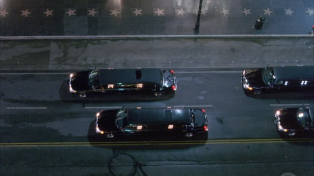 HIGH ANGLE DOWN OF FOUR BLACK LIMOS PARKED ON STREET. SEE HOLLYWOOD STARS ON SIDEWALK ON TOP.