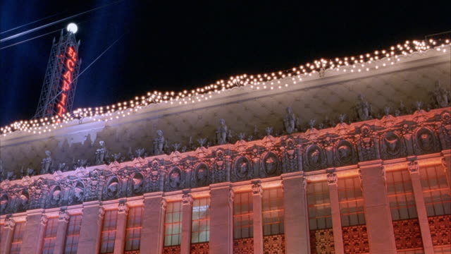 """up angle of el capitan theatre. see lights hanging from roof edge. see neon sign that says """"el capitan"""" vertically extended from roof. red light reflected off of building. hollywood. movie theaters. beams of light from klieg lights scan back and forth. co - el capitan kino stock-videos und b-roll-filmmaterial"""