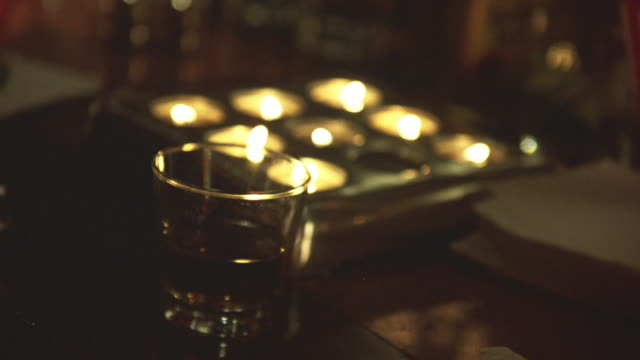 close angle of cup of alcohol on wooden table. could be in bar. see 9 candles in 3 by 3 configuration behind cup. see stack of napkins beside candles. - napkin stock videos and b-roll footage