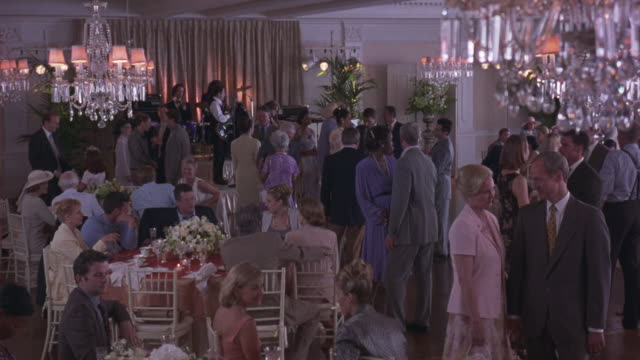medium angle of people at a banquet or dance. could be charity or fundraising event. see men in suits and women in dresses. see plastic or crystal chandeliers. see band in the background. - festmahl stock-videos und b-roll-filmmaterial