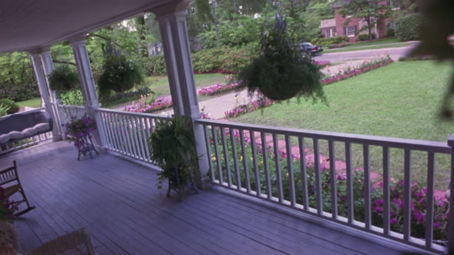 vidéos et rushes de medium angle of veranda or porch and front yard. see hanging potted plants. see wooden fence enclosing porch. see purple flowering plants bordering lawn and entrance to driveway. see houses and streets in the background. see black sedan drive right to lef - limousine voiture