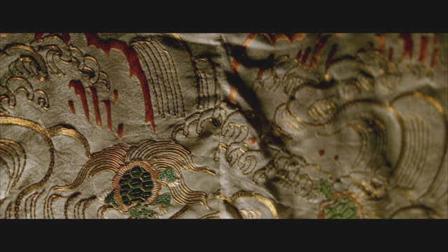 CLOSE ANGLE OF JAPANESE TAPESTRY OR BLANKET WITH GOLD TRIM, ART DEPICTING WAVES, TURTLES.