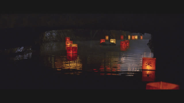 pan up of river or stream with floating candle-lit japanese paper  lanterns, bridge, towns,  buildings, porches, rickshaw, pedestrians, men and women. cherry blossom trees. beauty shot. - lantern stock videos & royalty-free footage