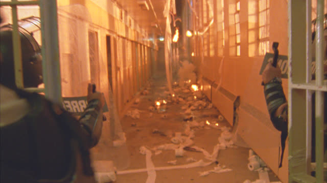 vídeos de stock, filmes e b-roll de medium angle from behind swat team at prison or jail raid. papers litter floor. fires. swat team enter prison cell area with shields and smoke bombs. smoke fills air. - explosivo