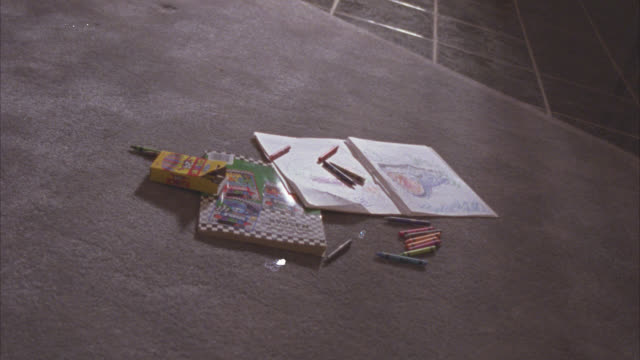MEDIUM ANGLE OF COLORING BOOK AND CRAYONS ON CARPET RUG. COULD BE LIVING ROOM OF HOUSE. TILE FLOOR IN BG. CHILD'S TOY.