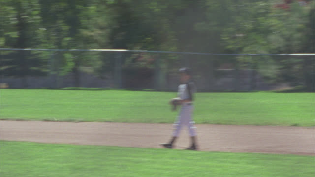 vídeos de stock e filmes b-roll de medium angle of adolescent boys playing baseball. uniforms. baseball fields. little league. boy empties bucket of baseballs onto field. sports. - camisola de basebol