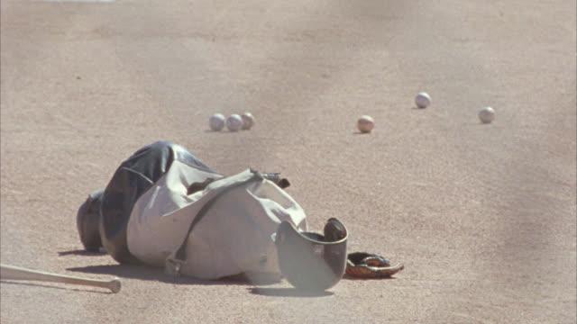 vídeos y material grabado en eventos de stock de medium angle of bag of baseballs lying on baseball field or diamond. baseball bat, helmet, and gloves lie on field. sports. - guante de béisbol