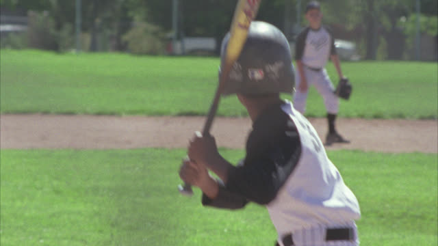 vídeos de stock e filmes b-roll de medium angle of adolescent boys playing baseball. boys wear uniforms. could be little league. baseball field. game or sport. - camisola de basebol