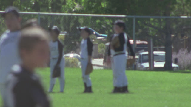 vídeos de stock e filmes b-roll de medium angle of adolescent boys playing baseball. boys wear uniforms. could be little league. baseball field. game or sport. boys pick up balls from field. could be end of game. - camisola de basebol
