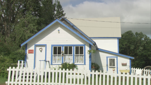 medium angle of small, white country house with blue trim. white picket fence surrounds lawn. rural area with trees behind house. lawn ornaments in grass. small towns. power lines. - picket fence stock videos and b-roll footage