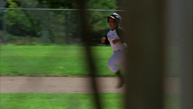 medium angle through chain link fence of adolescent boys playing baseball. boys wear uniforms. could be little league. baseball field. game or sport. home runs. - little league stock videos and b-roll footage