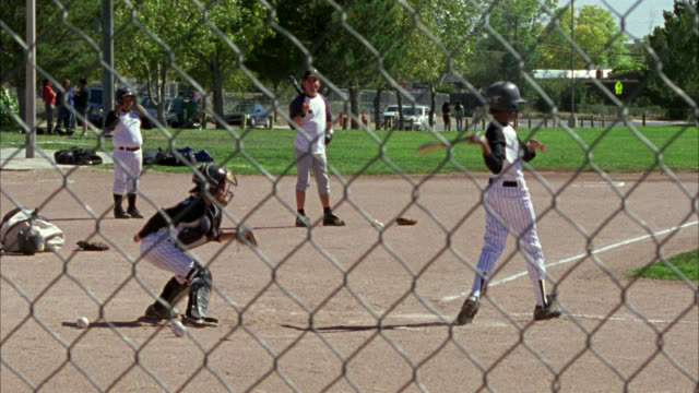 medium angle through chain link fence of adolescent boys playing baseball. boys wear uniforms. could be little league. baseball field. game or sport. - baseball strip stock videos & royalty-free footage