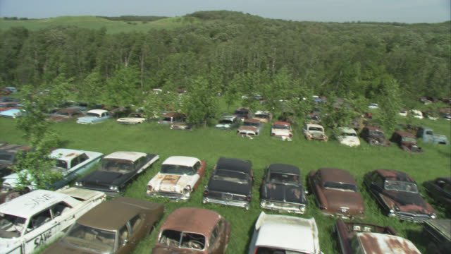 high angle down of rural junkyard filled with old cars. camera cranes down to ground level pov. rows of rusted and broke down vintage cars and trucks lie in tall grass field. grassy hills, forest, woods, trees in background. strong wind blowing trees. rur - hill stock videos & royalty-free footage