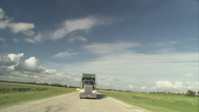 process plate of front of semi truck following behind camera on rural area highway. semi accelerates and follows close behind, then drifts behind. could be car chase. shot passes by fields or farmlands. clouds in sky. freight train to right of highway. - 大型トレーラー点の映像素材/bロール