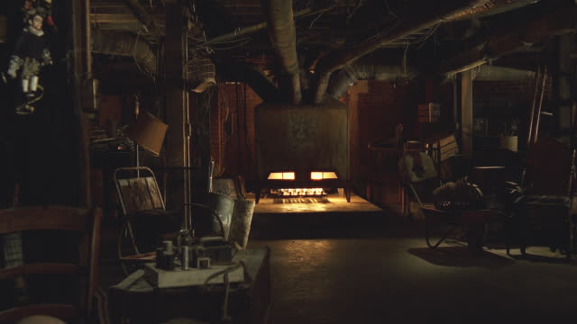 wide angle of large, lit furnace in dark, dusty, cluttered basement.  see air ducts extending along ceiling from furnace.  see flames through openings on  furnace which resemble a creepy looking head and face.  camera pans left to show creepy marionette o - marionette stock-videos und b-roll-filmmaterial