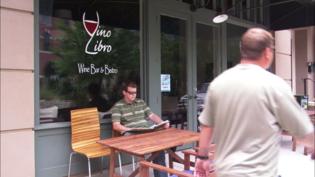 """pan down a restaurant, cafe, bistro, or wine bar.  the glass window reads """"vino libro wine bar & bistro."""" a man reads a newspaper on the table outside. - wine bar stock videos & royalty-free footage"""