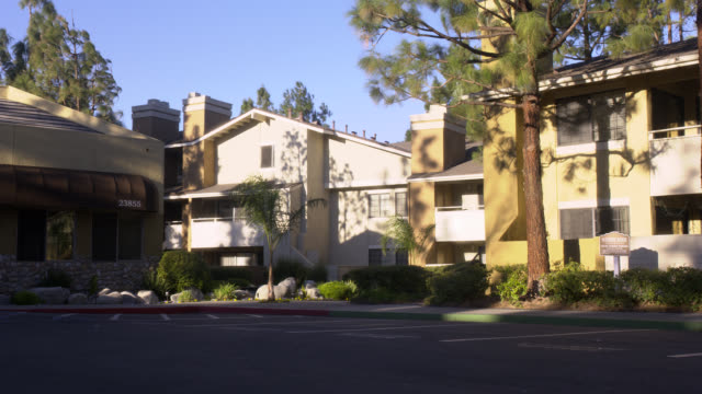 wide angle of a small apartment complex community style in suburban area. pine trees, sidewalks, awning, blue sky. actual address is stone creek apartment homes at 23855 arroyo park drive in valencia, california. middle class. - middle class stock videos & royalty-free footage