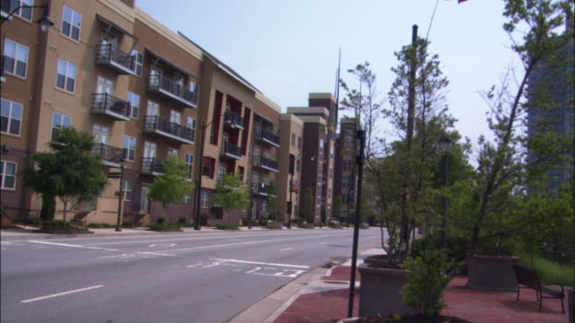 """hand held angle a suburban apartment building. several cars drive past the corner of the intersection down a street or road.  a sign reads """"icon"""" on the front of the  condo or condominium. - corner stock videos & royalty-free footage"""