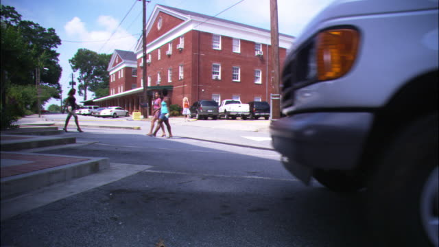 "stockvideo's en b-roll-footage met wide angle of pedestrians crossing main street in small town. three story brick building in background. could be post office, government building or town hall. delivery truck pulls into frame and parks. could be courier service. logo on door reads ""state - georgia us state"
