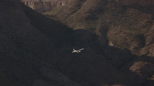 a-a aerial tracking shot of propeller plane flying over desert canyon or valley. single propeller airplane is white. air-to-air. - propeller video stock e b–roll