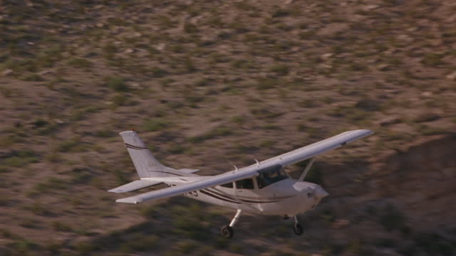 a-a aerial tracking shot l-r of small propeller airplane flying over desert landscape. plane flies over desert canyons, valleys and hills with sparse vegetation. briefly flies over river reflecting clouds and sky. air-to-air. - propeller video stock e b–roll