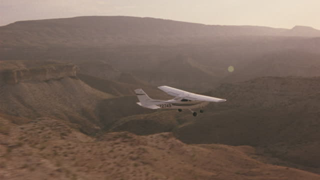 a-a aerial tracking shot l-r of small propeller airplane flying over desert landscape. plane flies over desert canyons, plateaus, cliffs and mountains  with sparse vegetation. river canyon visible briefly. zoom in to cockpit showing pilot and passenger. t - propeller aeroplane stock videos & royalty-free footage
