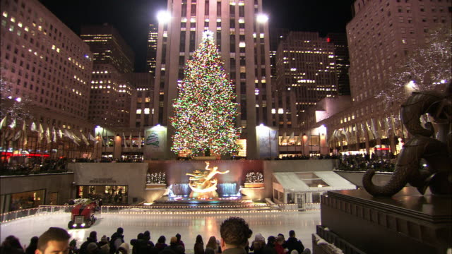 vídeos de stock, filmes e b-roll de pan right to left to christmas tree decorated with lights in rockefeller center. 30 rock, ge building. skyscrapers or high rise office buildings. ice skating rink. midtown manhattan. landmark. - centro rockefeller