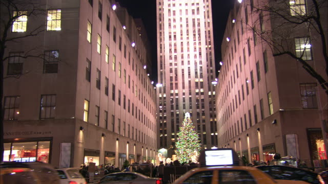 pan right to left from rockefeller center christmas tree to people looking at window displays. christmas decorations. saks & company, fifth avenue. pedestrians. skyscrapers or high rise office buildings, ge building, 30 rock. christmas lights. midtown man - rockefeller center christmas tree stock videos & royalty-free footage