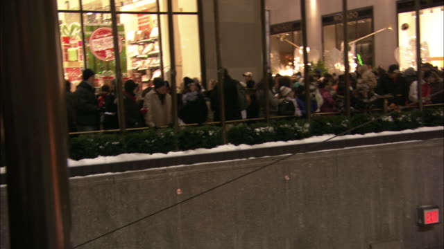 pull back from crowd on stairs to people ice skating in rink to christmas tree with lights and decorations in rockefeller center. statue and fountain. skyscrapers or high rise office buildings. ge building, 30 rock. midtown manhattan. - rockefeller center christmas tree stock videos & royalty-free footage
