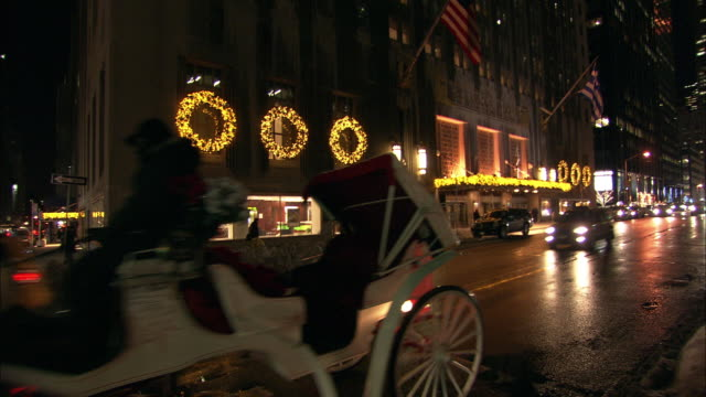PAN RIGHT TO LEFT ACROSS PARK AVENUE TO THE WALDORF ASTORIA HOTEL. UPPER CLASS. SNOW. CARS ON CITY STREET. CHRISTMAS LIGHTS AND DECORATIONS. HORSE-DRAWN CARRIAGE. MIDTOWN MANHATTAN.