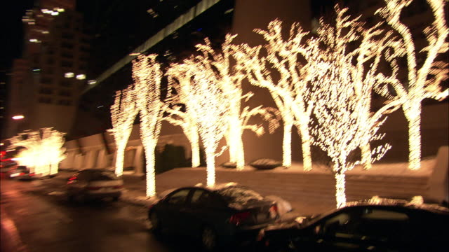 medium angle moving pov on w 58th st past christmas lights or decorations on trees near paris theater. midtown manhattan. city streets. - paris theater manhattan stock videos and b-roll footage