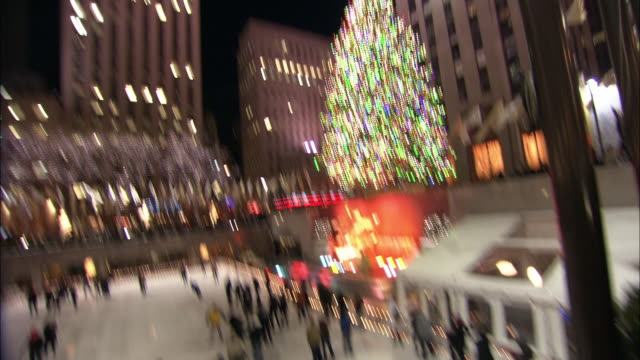 pan up from people ice skating in rink to christmas tree with lights and decorations in rockefeller center. statue and fountain. skyscrapers or high rise office buildings. ge building, 30 rock. midtown manhattan. - rockefeller center christmas tree stock videos & royalty-free footage