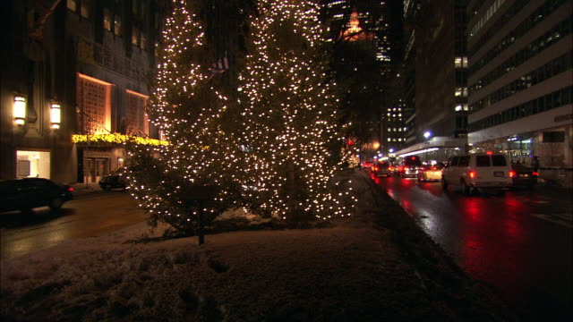 PAN RIGHT TO LEFT ACROSS PARK AVENUE TO THE WALDORF ASTORIA HOTEL. UPPER CLASS. SNOW. CARS ON CITY STREET. CHRISTMAS LIGHTS AND DECORATIONS. MIDTOWN MANHATTAN.