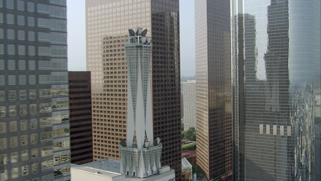 AERIAL LOW-SPEED FLYING POV THROUGH  DOWNTOWN LOS ANGELES SKYSCRAPERS AND HIGH RISES. PAN AROUND OF CITY SKYLINE AND GLASS OFFICE BUILDINGS. WESTIN BONAVENTURE HOTEL.