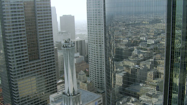 AERIAL LOW-SPEED FLYING POV THROUGH DOWNTOWN LOS ANGELES CITY SKYLINE WITH SKYSCRAPERS, HIGH RISES, AND GLASS OFFICE BUILDINGS. WESTIN BONAVENTURE HOTEL.