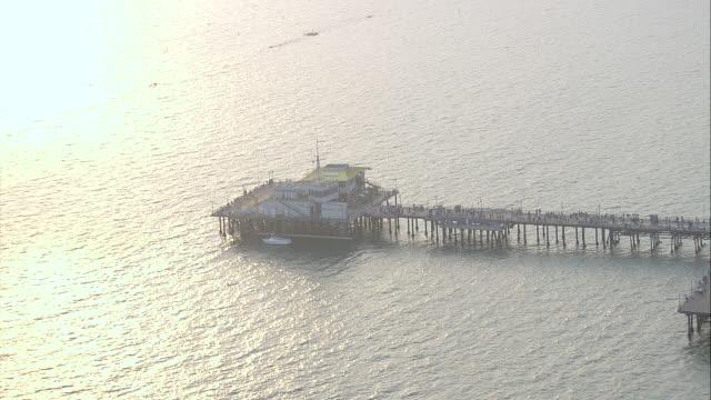 aerial of santa monica pier, beach, dock, and amusement park. palm trees, pacific ocean, pacific coast or coastline visible. - pacific coast stock videos & royalty-free footage