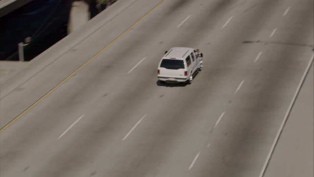 aerial of swerving white suv or speeding car merging onto highway or 105 freeway as police cars chase from behind. men from driver and passenger seat pull out guns. gunfire. police action. police chase. los angeles police. - motorway stock videos & royalty-free footage